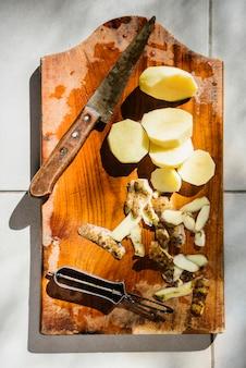 Vista alta ângulo, de, cortado, batatas, com, faca, ligado, madeira, tábua cortante