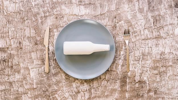 Vista alta ângulo, de, garrafa branca, ligado, prato, entre, garfo, e, faca cozinha