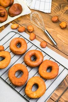 Vista alta ângulo, de, gostoso, caseiro, donuts, ligado, bandeja, perto, whisk, ligado, tabela textured madeira