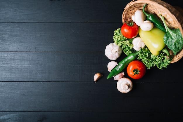 Vista alta ângulo, de, legumes crus, com, cesta vime, ligado, pretas, madeira, superfície