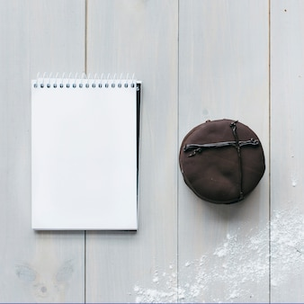 Vista alta ângulo, de, macaroon chocolate, e, em branco, notepad, ligado, prancha madeira