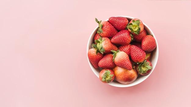 Vista alta ângulo, de, morangos frescos, e, maçãs, em, tigela, ligado, cor-de-rosa, fundo