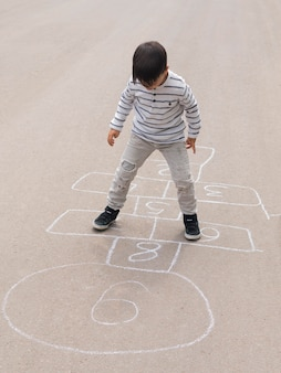 Vista alta criança brincando de amarelinha na rua
