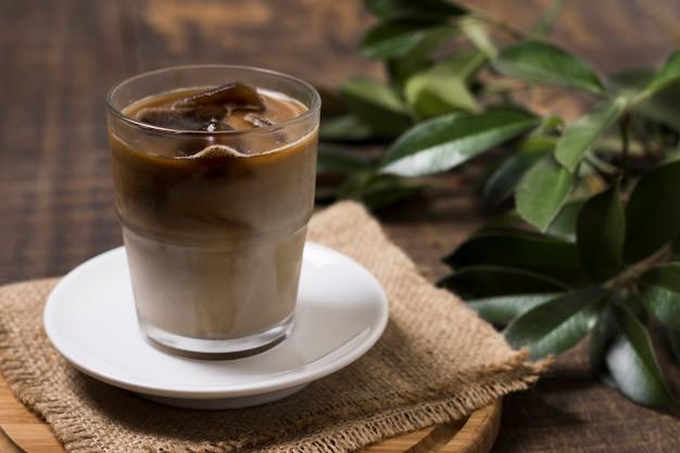 Vista alta deliciosa café em copo com pano