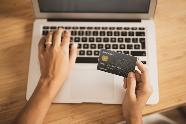 Vista alta do laptop e cartão de crédito para fazer compras
