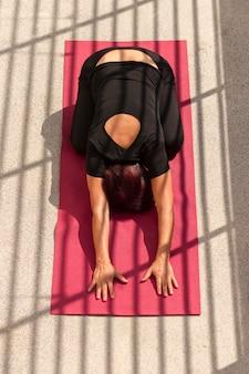 Vista alta mulher sentada em posição de ioga