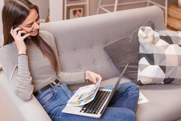 Vista alta mulher trabalhando em casa e olhando para gráficos