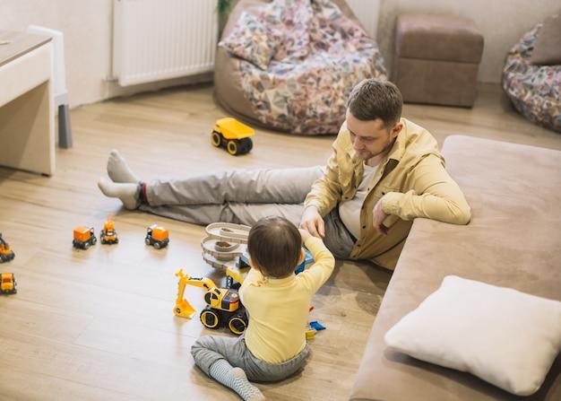 Vista alta pai e filho brincando com caminhões