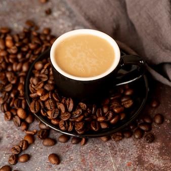 Vista alta xícara saborosa rodeada por grãos de café