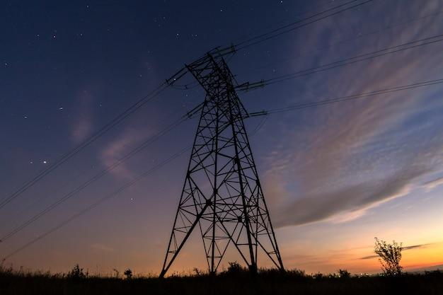 Vista angular da torre de alta tensão com linhas de energia elétrica, estendendo-se no céu estrelado azul escuro