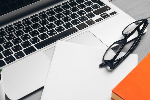 Vista angular do teclado do computador portátil e óculos com vários materiais de escritório na mesa de madeira