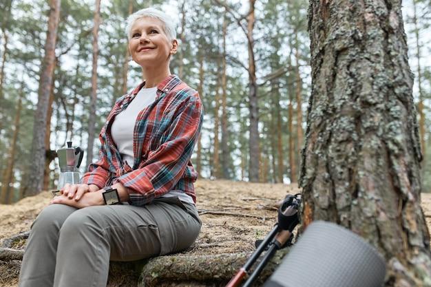 Vista ao ar livre do verão de uma atraente mulher aventureira de meia-idade sentada perto de uma árvore, fervendo água para o chá na chaleira, tendo um olhar alegre, admirando a bela natureza, pássaros cantando, sorrindo alegremente