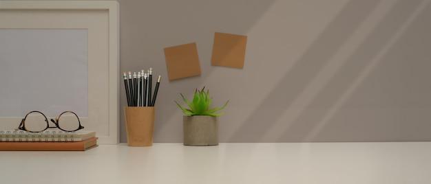 Vista aproximada da mesa de estudo com espaço de cópia, papelaria, óculos, decorações e bloco de notas na parede cinza