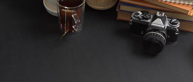 Vista aproximada da mesa de trabalho com espaço de cópia, câmera, livros e xícara de café na sala de home office