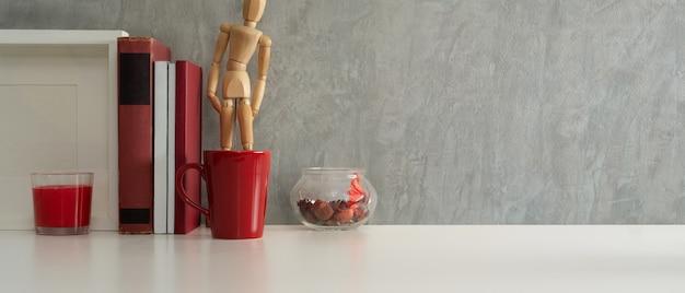 Vista aproximada da mesa de trabalho com livros, copo vermelho, moldura simulada e espaço de cópia no escritório doméstico