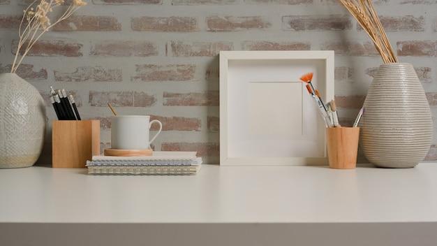 Vista aproximada da mesa de trabalho com moldura de papelaria e decorações na sala de home office