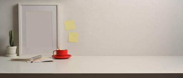 Vista aproximada da mesa de trabalho com simulação de fram, papelaria, xícara de café e espaço de cópia na sala de home office