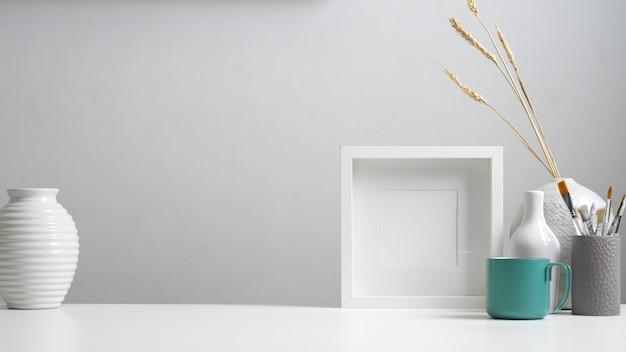 Vista aproximada da mesa do escritório em casa com espaço de cópia, moldura simulada, pincéis e decorações em conceito branco