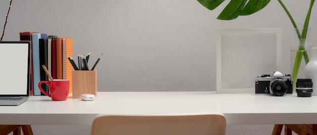 Vista aproximada do espaço de trabalho com simulação de laptop, artigos de papelaria, decorações, livros e espaço de cópia na mesa branca com cadeira