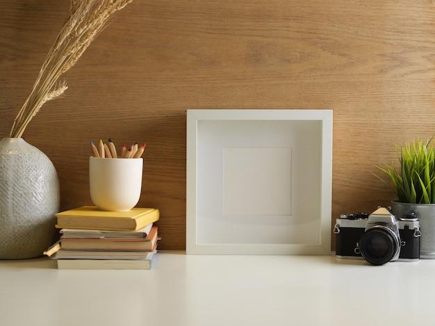 Vista aproximada do espaço de trabalho com simulação de moldura, câmera, artigos de papelaria e decorações na sala de escritório em casa