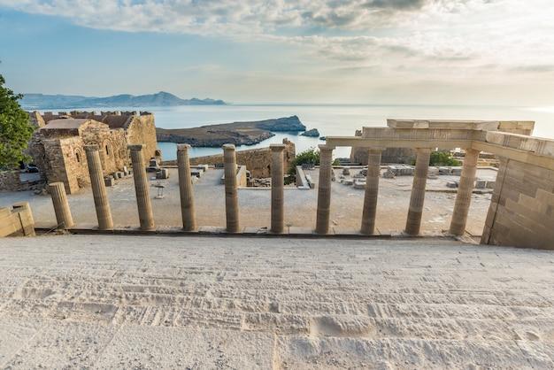 Vista através de antigos pilares em direção ao mar de uma bela acrópole de lindos.