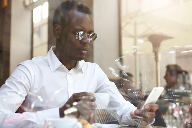 Vista através do vidro da janela do bisunessman preto bonito ou trabalhador corporativo vestindo tons redondos e camisa formal, tomando café e verificando o email no celular durante as férias no café moderno