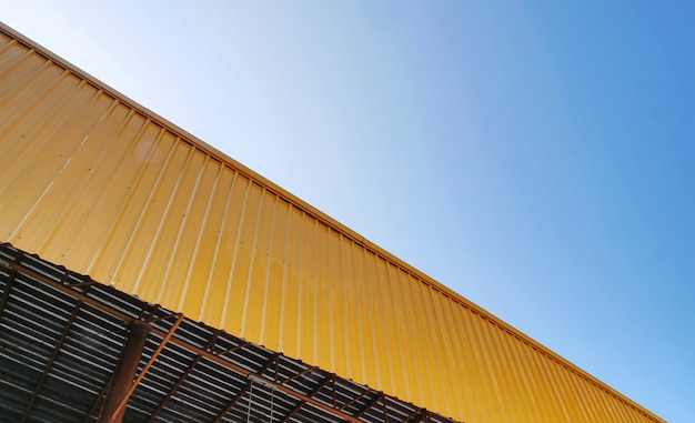 Vista baixa ângulo, de, amarela, telhado ondulado, exterior, contra, céu azul