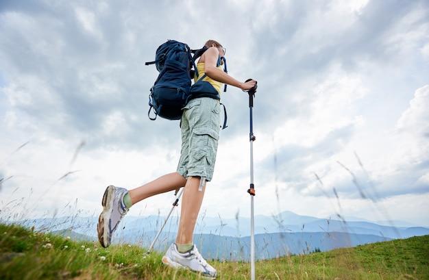 Vista baixa ângulo, de, atraente, mulher alpinista caminhadas na trilha de montanha, andando na colina gramada