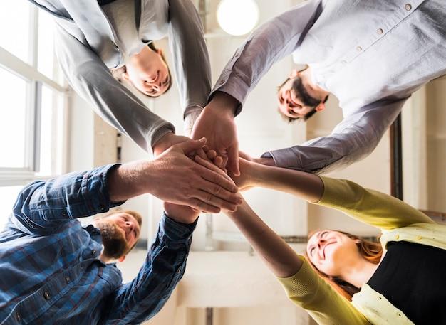 Vista baixa ângulo, de, businesspeople, empilhando, mão, junto, em, local trabalho