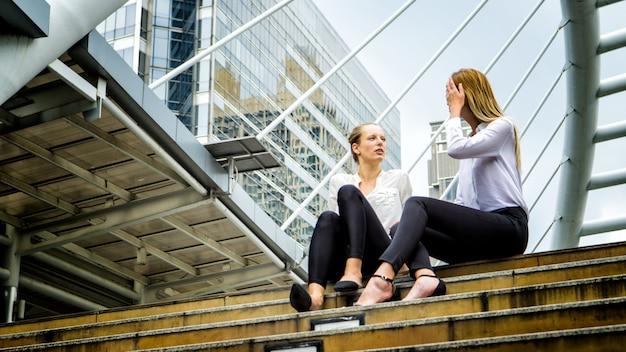 Vista baixa ângulo, de, femininas, colegas, discutir, enquanto, sentando passos, contra, predios, em, cidade
