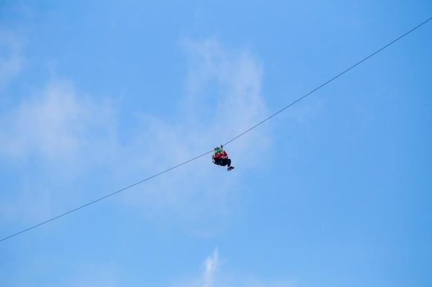Vista baixa ângulo, de, turista, montando, um, zip, linha, aventura, contra, céu azul