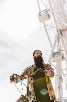 Vista baixa ângulo, de, um, homem jovem, montando, ciclo, perto, roda ferris