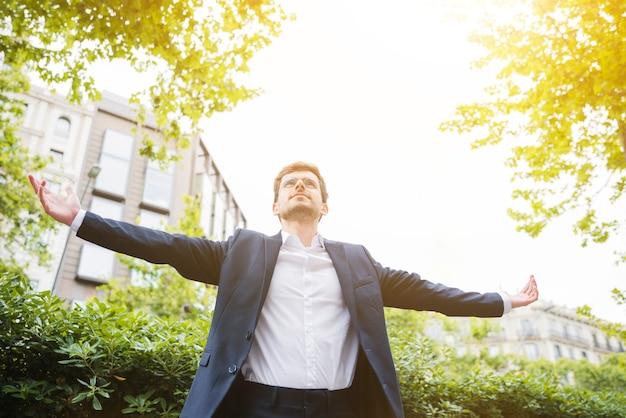 Vista baixa ângulo, de, um, homem negócios fica, frente, predios, outstretching, seu, braços