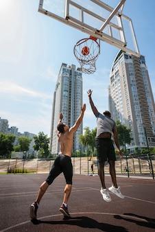 Vista baixa ângulo, de, um, homens jogando basquete