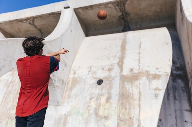 Vista baixa ângulo, de, um, menino adolescente, basquetebol jogando