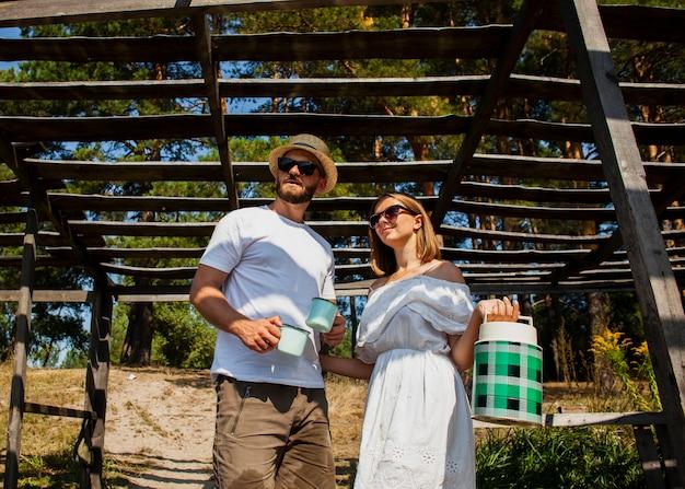 Vista baixa do casal olhando para longe e segurando um tanque de água