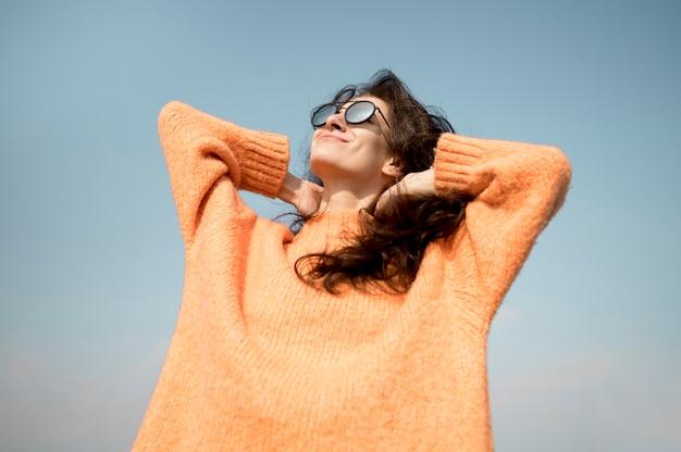 Vista baixa mulher bonita usando óculos de sol