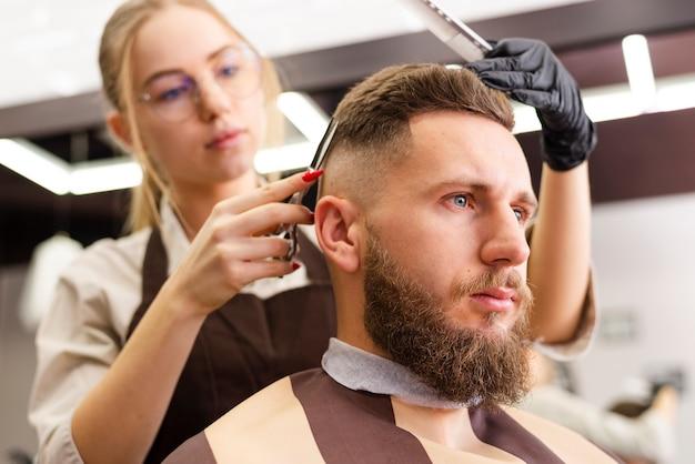 Vista baixa, mulher, cortar cabelo de um cliente