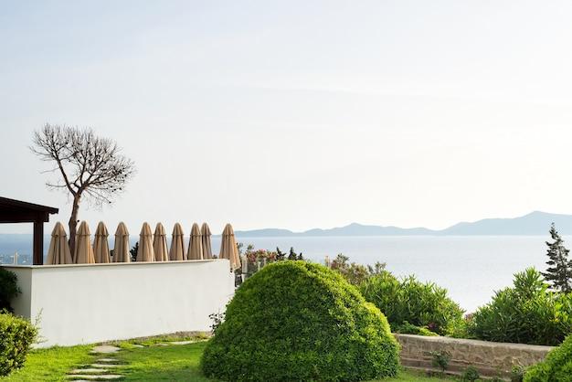 Vista bonita de plantas verdes e guarda-chuvas de praia e vista do mar e das montanhas.