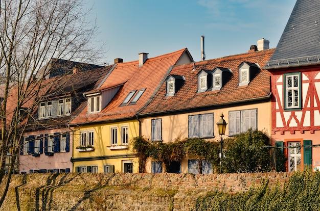 Vista bonita de um beco estreito pitoresco com casas tradicionais históricas e uma rua de paralelepípedos na cidade velha na alemanha com céu azul e nuvens no verão.