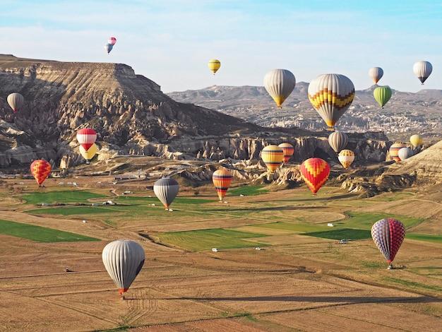 Vista bonita dos balões de ar quente coloridos que voam sobre a paisagem em cappadocia, turquia.
