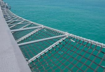 Vista bonita no oceano. Rede no lado do navio e da água azul.
