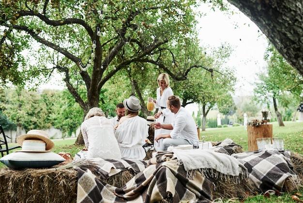 Vista bonita. o suco de laranja está chegando. grupo de amigos adultos descansam e conversam no quintal do restaurante na hora do jantar.