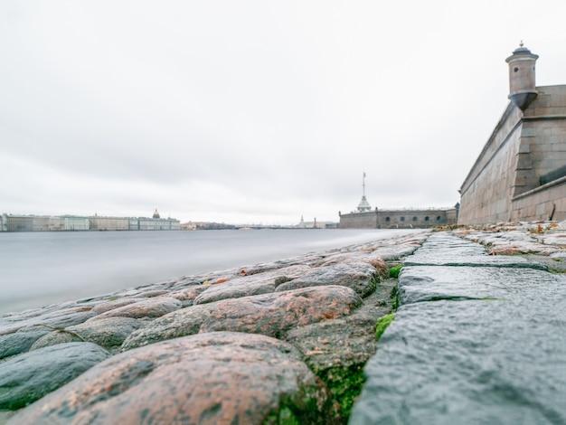Vista cinza do final do outono do pavimento de granito da fortaleza de pedro e paulo em são petersburgo. rússia. rio neva, longa exposição