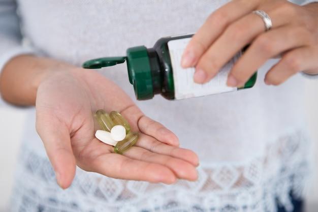 Vista colhida da mulher derramando comprimidos da garrafa