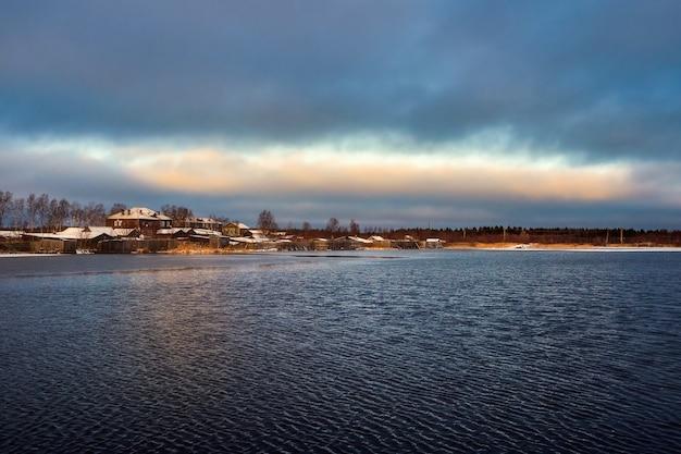Vista com casas antigas perto de um lago. autêntica cidade do norte de kem no inverno. rússia.