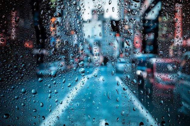 Vista conceitual da bela paisagem da cidade através de uma janela de vidro com gotas de chuva