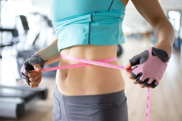 Vista cortada da mulher desportiva magro medindo a cintura