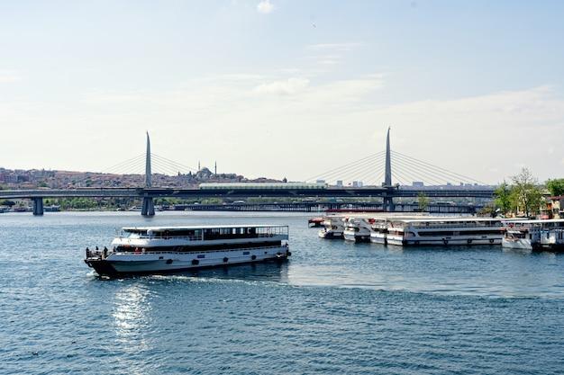 Vista da água para transportar na frente da ponte do trem do metrô de suspensão na estação de metrô halic chifre dourado de istambul