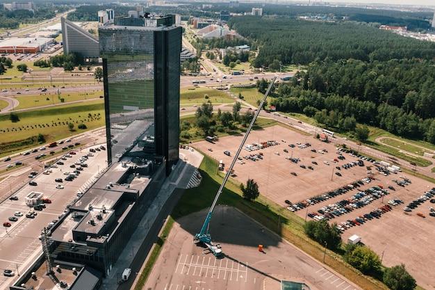 Vista da altura do guindaste mais alto do carro, que está aberto no estacionamento próximo ao prédio de vidro da cidade e pronto para funcionar. o guindaste móvel mais alto é implantado no local.
